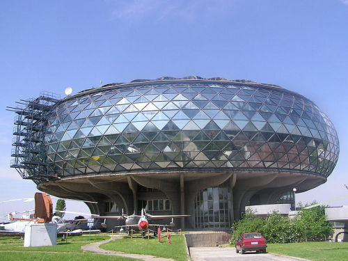The Museum of Aviation in Belgrade was founded in 1957 as the Yugoslav Aeronautical Museum. The facility is located adjacent to Belgrade Nikola Tesla Airport. The current facility, designed by Ivan Straus, opened to the public on May 21, 1989. The main collection is housed in an architecturally noteworthy, geodesic-based, glass building, with additional aircraft displayed on the surrounding grounds. The collection contains over 200 aircraft, 130 aviation engines, several radars and missiles. In the lobby of the museum, one can find a gift shop, aviation models, an information centre and a contemporary cinema hall. (via Aeronautical Museum Belgrade, Ivan Straus | Belgrade | Serbia | MIMOA)