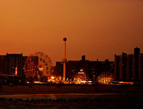 "Coney Island beach at sunset with the Wonder Wheel and the Cyclone. Brooklyn, New York City.  Coney Island is the site of my favorite New York City beach. The Rockaways in Queens have become popular over the last few years and while I have fond memories of the Rockaways (since I grew up in Queens) Coney Island tugs at my heart in the best way possible. There is nothing like standing on the old pier that juts out into the Atlantic ocean while watching the waves crash onto the shore as the lights on the Wonder Wheel and the Cyclone twinkle in the distance like a tiny city of candles.  When I was much younger, I moved to New Mexico for a year and a half. I was in high school at the time and many fellow students would ask me what it was like to live so close to the ocean and I could never quite explain what it was like at the time. I was always at a loss for words. It was what I grew up with and it was hard for me to imagine life without access to the ocean.  Years later, it's still hard to fully put into words what it is like: breathing in salty ocean air, viewing the night sky while listening to waves, the feel of cool sand on bare feet, jumping through the ocean with wild abandon.   I think I keep taking photos in an attempt to further explain what the ocean means to me. Isn't that why we write, take photos, paint, dance, create music and engage in a variety of other artistic pursuits? It's to put into form those feelings and experiences that remain otherwise formless.  —-  View this photo larger and on black on my Google Plus page —-  Buy ""Coney Island Beach at Sunset - Brooklyn - New York City"" Prints here, email me, or ask for help."