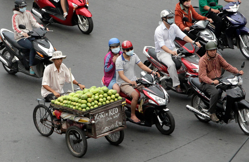 A fruit vendor on a bicycle travels next to people on motor scooters in Ho Chi Minh City on April 3, 2012. (Nick Ut/Associated Press) #