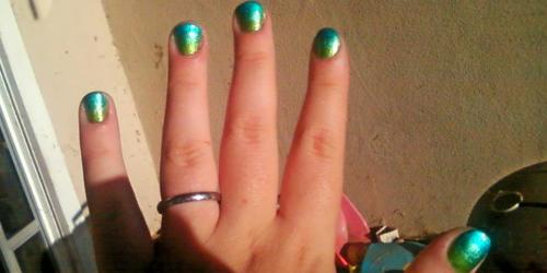 "My nails, so far. Here's what I've done. Buffed nails with a four-sided nail buffer. I got mine from the dollar store, honestly. I need to get a new one, because I've had it for a few months and you get what you pay for, but I love these things. Solid layer of the green - I used Wet n Wild ""Sage in the City"" because I love the sage green! I did two coats because I personally hate translucent base colors, but that's just me. They look cute on other people but I don't like them on me. About 1/3 of the way down, I used my second color - Sinful Colors ""Gorgeous"", a lovely teal green. I have had my SC polishes since Valentine's Day, but I rarely use them because they're translucent and, as stated for step 2, I don't particularly care for translucent nails. This multi-colored thing is still very new to me. Another 1/3 of the way down I used my third color - Sinful Colors ""Love Nails"". Read explanation for step 3; it's basically the same. I still have black that I'm trying to find a way to incorporate, but I haven't decided yet what to do with it."