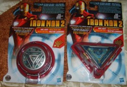 Tony Stark's ARC Reactor & Mark VI ARC ReactorMovie: Iron Man IIBrand: HasbroYear: 2010Description: Tony Stark's ARC reactor and the ARC reactor as seen when he's wearing MARK VI armor.Additional information: when the center of both reactors is pressed, it emits sounds and lights. the lights are yellow (personally I would've preferred them with blue LEDs instead of yellow ones), and there's no way to keep them permanently on.Even so, the level of detail, considering that they're made out of plastic, is quite good.Both ARC reactors could be attached to the clothes with another piece of plastic.
