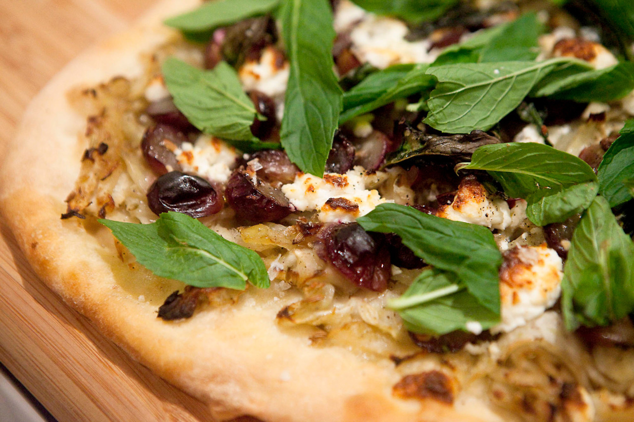 Caramelized Fennel, Grape, Goat's Cheese and Mint Pizza I'm finally getting the hang of how to make an awesome pizza with a crispy crust.  I've frozen some pizza dough as well to see if I can uncomplicate the process and be able to make a quick pizza on a weeknight. I made this pizza dough recipe, and after it rose, I split it into balls and wrapped it in oiled cling film and popped it in the freezer.  To thaw, remove the cling film from the dough and pop it in a bowl covered with a damp towel or cling film.  Leave it on the counter (not the fridge) for the day to thaw and rise.  For breakfast pizza, do this overnight.  You can also make bread or rolls out of this dough, it's a really nice recipe, just make sure to use the Type 00 flour. Ingredients: 1 portion of pizza dough 1 fennel bulb, shaved 2 tbsp sugar 1 tbsp fennel seeds 1 cup of grapes, cut in half 1/4 cup crumbled goat's cheese 1/2 cup mint leaves Olive oil, salt and pepper Turn on the oven as hot as it will go for at least 30 minutes to preheat.  After 10 minutes, put your pizza stone in the oven to get it hot.  This is very, very important to get crispy crust on the bottom. In a warm pan with olive oil, saute the fennel until soft.  Add the sugar, fennel seeds, and season with salt and pepper.  Cook on medium low, stirring occasionally, for about 10 minutes to caramelize.  It will turn a bit golden and get quite soft. Flour a cutting board or the counter very well, and spread the pizza dough into a rough circle.  Let rest for 10 minutes, and then spread it again to get a 15 inch pizza.  Remove the pizza stone from the oven, and using a rolling pin or wine bottle, slip it under the dough (so it's only touching the floured side) to help move it onto the stone.  Layer on the fennel (depending on the size of your bulb, and your love of fennel, you may or may not use it all), a couple of the mint leaves, the grapes, and the goat's cheese.  Season with salt and pepper and bake for about 10 minutes until the crust is golden. Sprinkle with mint leaves to finish, and here's the other piece… leave it on the stone out of the oven for about 5 minutes before you go to cut or eat it.  The stone will keep cooking the base, but you're not burning the cheese by leaving it in the oven.  Score.