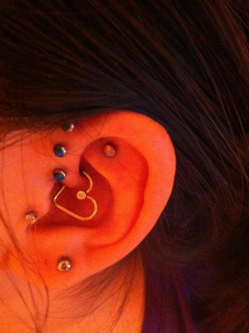 My new ear-heart and tash-rook piercings. Aren't they amazing? I'm simply stunned by the elegance of the ear-heart. I can't stop looking at it! BVLA 14kt yellow gold with authentic diamond ear-heart. Purchased from Haven body arts, Mass. and pierced by Jamie of Saint Sabrina's Minneapolis. ;)