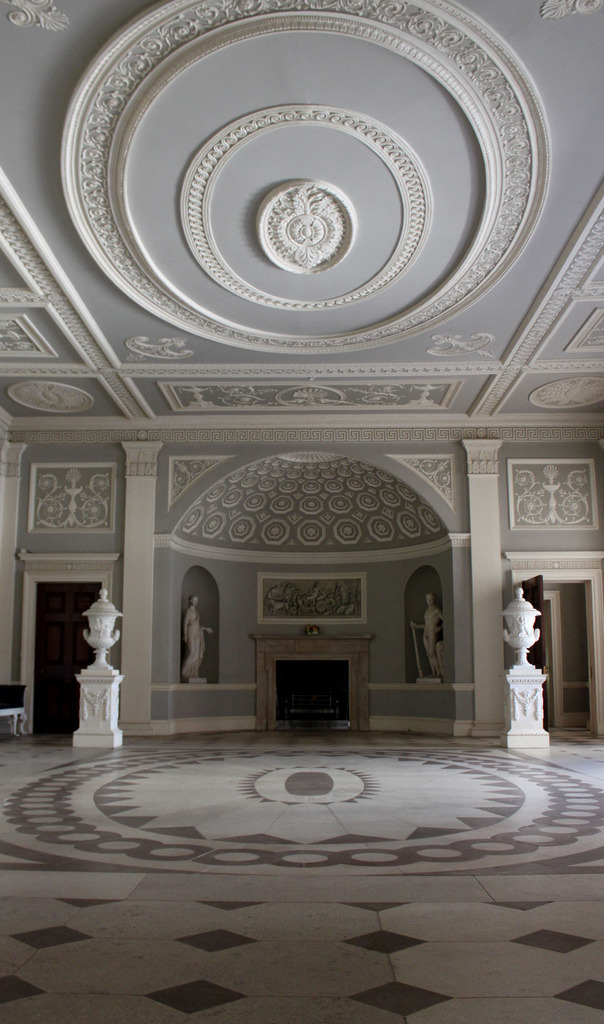 Entrance Hall: South Apse ~ Osterley Park House You can see from this shot that the floor and ceiling echo each other in design. The Stucco work was executed by the firm of Joseph Rose and the grisaille paintings above the fireplaces are by Giovanni Pattista Cipriani.  The Entrance Hall was created in 1767. It fulfils Robert Adam's great desire to bring 'movement' of shapes, light and shadow to a space. Its rectangular shape is enhanced by semicircular alcoves at each end, both with a fireplace flanked by niches filled with statues. Constructed as an all-purpose room, the Hall was used as a saloon, reception room and occasional dining room. Stucco panels of military trophies adorn the walls, inspired by the marble trophies of Octavianus Augustus on the Campidoglio in Rome. Adam created similar stucco trophies for the vestibule at nearby Syon Park. The patterned floor is fashioned in white Portland stone and red sandstone. The chimney pieces, also in Portland stone, are embellished with the Child family crest of an eagle holding an adder in its beak.