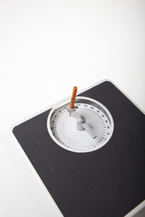 razorshapes:  The Weight Recorder basically records the changing weight of a person over a period of time, it makes marks on a disk that responds to the passed life. The device is a mechanical scale with a compass holding a pencil that can draw lines on the tracing paper disk attached to the statistical part. When the user stands on the scale, the compass turns and the pencil draws an arc. The radius of the compass can be adjusted in every usage, so the arcs are drawn concentrically. The user can use the devices over a certain period of time, eventually the user will get a graphical 'life-tracing' on a disk.