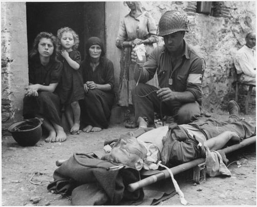 taco-man-andre:  Private Roy W. Humphrey of Toledo, Ohio is being given blood plasma after he was wounded by shrapnel in Sicily on 8/9/43