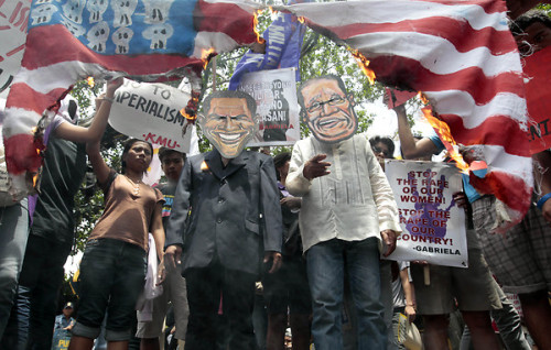 thepeoplesrecord:  Filipino activists don masks of US President Barak Obama (L) and Philippine President Benigno Aquino III (R) during a burning of a mock American flag during a rally against USA's presence in the country, outside the gates of the US embassy in Manila, Philippines, 08 June 2012. Members of militant group BAYAN MUNA flocked to the US Embassy to denounce the presence of American troops in the Philippines. The protesters in their statement condemned the visit of Pres. Aquino to the United States which further reaffirm Philippines-US ties.