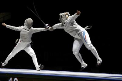[ID: two sabre fencers in a bout. The one on the left is lunging as her opponent flunges.] Egorian (left) against Boudiaf!