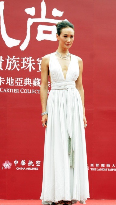 The elegant Maggie Q shows a bit of cleave [and rib] in a white deep-v dress at a jewelry exhibition held in the National Palace Museum in Taipei