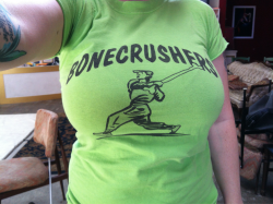 "Day 130: BONECRUSHERS! I bought this shirt at a thrift store a long time ago, probably savers, probably 4 years ago when my spending was merciless because I didn't understand how credit worked. It was too big so I altered it to fit me because it was lime green and said ""BONECRUSHERS"" and the baseball guy is using a bone for a baseball bat. It also has a large plasticy number 6 on the back, which means it was totally a jersey, for some amazingly cool baseball team called BONECRUSHERS. BONECRUSHERS!!"