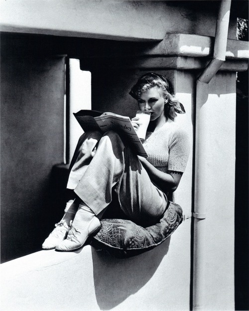 books0977:  Ginger Rogers reading Romola Nijinsky's Life of Nijinsky, assisted by Lincoln Kirstein (1933). Ginger Rogers (1911-1995) was an American actress, dancer, and singer. Rogers more often than not had a book in her face.  Her mother once remarked that it was hopeless to read a book after Ginger had read it.  She marked it up with notes.  She was always trying to improve herself.