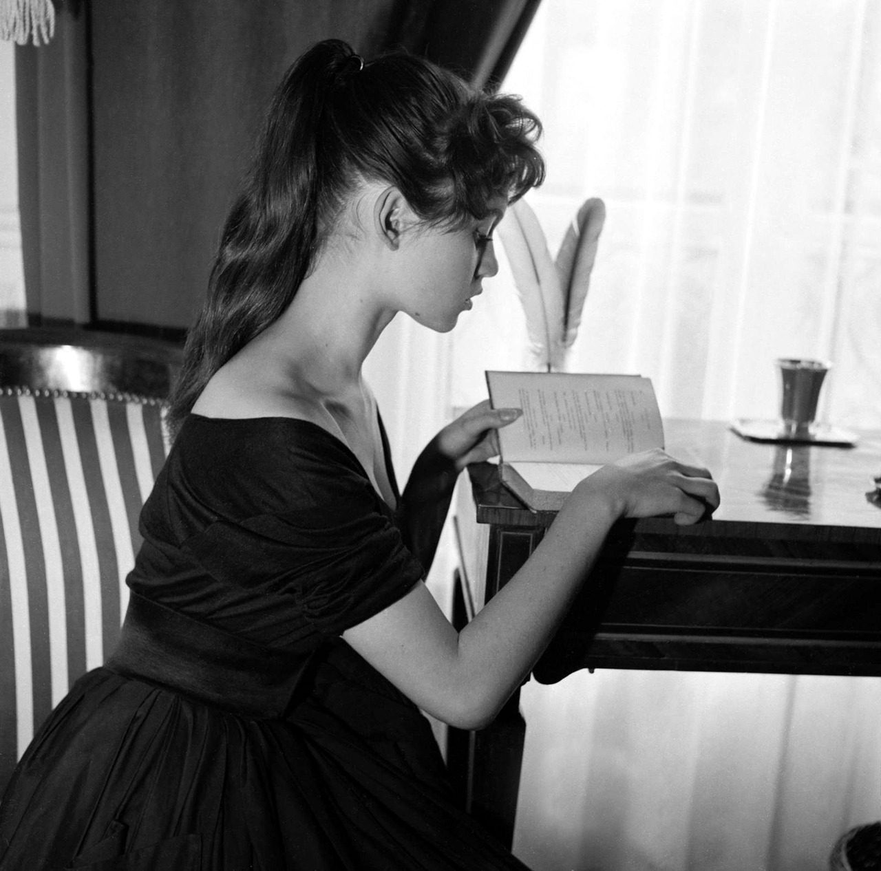 "Brigitte Bardot reading a book at her home, Paris, 1955. Gaston Paris Photoshoot. Bardot (1934-), at 15, was trying a modeling career, and found herself in the French magazine ""Elle"". Her incredible beauty readily apparent, Brigitte next tried films. She appeared on screen for the first time as Javotte Lemoine in Le Trou Normand (1952). ""I started out as a lousy actress and have remained one."" - Brigitte Bardot"
