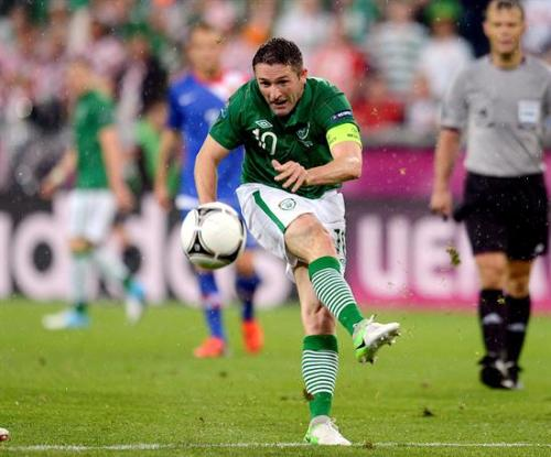 Robbie Keane of Ireland takes a shot whilst wearing the Nike Total 90 IV White/Green clash collection.