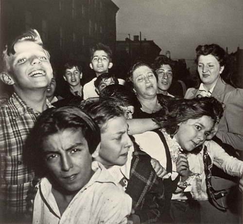 "cavetocanvas:  Weegee, Their First Murder, October 9, 1941 From the Getty Museum:  ""A woman relative cried…but neighborhood dead-end kids enjoyed the show when a small-time racketeer was shot and killed,"" wrote Weegee in the caption accompanying this startling photograph in his 1945 publication Naked City. On the facing page Weegee showed the bloody body lying in the street. Alternately laughing, staring in disbelief, or looking into the camera to grasp their own momentary chance to be recorded, the children who had witnessed this grisly scene form an unsettling amalgam of human emotion and self-absorption. Two women are among the group: one, whom Weegee mentioned above, stands at the center, her face contorted with anguished tears, her personal loss turned into public spectacle."
