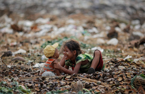 politics-war:  A girl plays with her brother as they search for usable items in a junkyard near the Danyingone station in Yangon's suburbs. Photo: Damir Sagolj