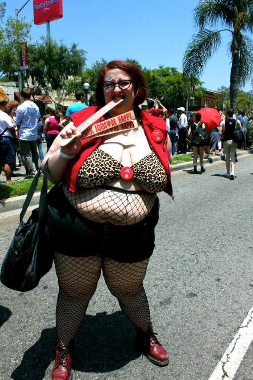 "lillianbehrendt:  [PHOTO: Fat white woman with short red hair and glasses biting a paint-stirrer that says ""Spank Someone Happy"" on the street wearing a leopard bikini top, red denim jacket, fishnet hose, black shorts and red boots. She has a silver streak on one side of her face.]"