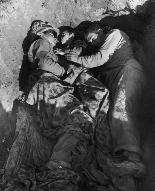 A pair of sleeping American Marines share their foxhole with an Okinawan orphan, 1945. LIFE