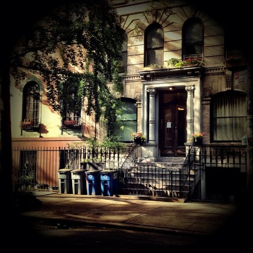 "All summer in a moment. St. Marks Place brownstone. East Village, New York City.  One of my favorite short stories by Rad Bradbury when I was really little was one of the first I ever read by him: All Summer in a Day. It's a story that revolves around a small group of children who live on Venus where it rains constantly and where the sun only comes out for a few hours every seven years.   I remember being struck in such a profound way with how one of the only children who remembers the sun describes the sun to the other children who have never experienced sunlight before since they are too young to have lived through their first sighting of the sun. It's something that has stuck with me for years.   I won't give away the ending or the rest of the plot but I was reminded of Bradbury's story when I took this photo with my phone the other day (in a rather tongue-in-cheek way). For the last month or so the weather in New York City has been extremely temperamental. While the sun hasn't disappeared entirely, it seems to make a grand entrance for a few moments or an hour or two before retreating behind storm clouds every day.   This photo was taken during one of the brief yet spectacular moments that the sun came out the other day. I just happened to be in front of one of my favorite facades on St. Marks Place and as the sun broke through the shadows of the trees decked out their finest summer foliage, my breath was taken away.   This is my weekly mobile photography post. I am @newyorklens on Instagram (view my feed here).  Check out my other Instagram posts made to this blog here. You can check out all of my Instagram photos on Flickr here. Additionally, you can view my phone photography for sale here.  —-  View this photo larger and on black on my Google Plus page   —-  Buy ""All Summer in a Moment - Brownstone - St. Marks Place - East Village - New York City"" Prints here, My mobile photography for sale here, My regular photography for sale here, email me, or ask for help."