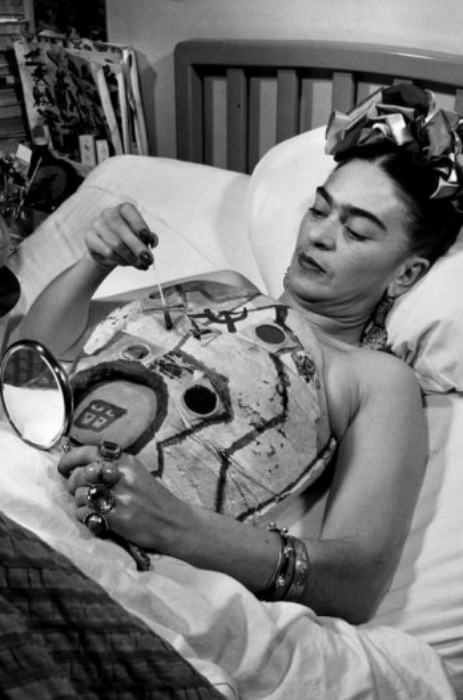Frida Kahlo in a hospital bed, drawing her corset with help of a mirror by Juan Guzmán, 1951 Frida Kahlo wore plaster corsets for most of her life because her spine was too weak to support itself. She painted them, naturally, covering them with pasted scraps of fabric and drawings of tigers, monkeys, plumed birds, a blood-red hammer and sickle, and streetcars like the one whose handrail rammed through her body when she was eighteen years old. The corsets remain to this day in her famous blue house—their embedded mirrors reflecting back our gazes, their collages bringing the whole world into stricture. In one, an open circle has been carved into the plaster like a skylight near the heart. Frida's corsets hardened around unspeakable longing. They still frame an invisible woman, still naked in her want, still calling to deaf men in the rain. I find them beautiful. She would have given anything, perhaps, to have a body that rendered them irrelevant. [ftp]