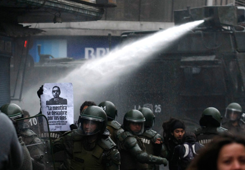 antisocial-socialist:  Santiago, Chile: Riot police use a water cannon to disperse a demonstration against the late general Augusto Pinochet.