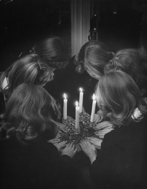 Six HS sorority girls re-enacting solemn, secret initiation ritual by candlelight for photographer because only a real member has ever seen the real thing. December 11, 1944.