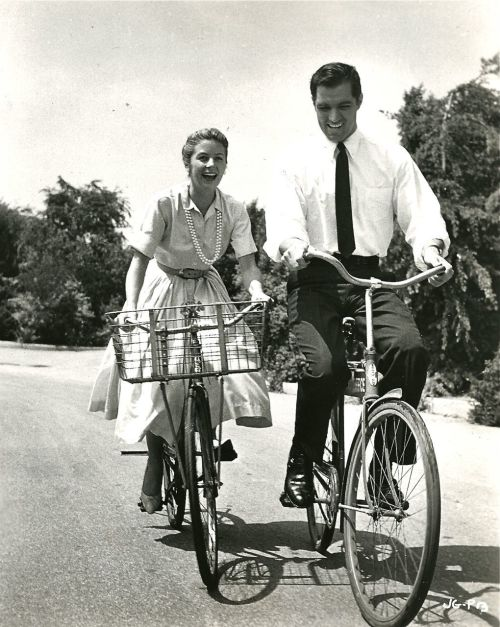 John Gavin and Cicely Evans ride bikes.