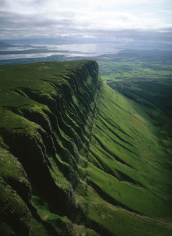 dequalized:  Ben Bulben, a large rock formation in County Sligo, Ireland. The formation has been listed as a protected structure. Photo by Jason Hawkes. Ben Bulben was formed during the Ice age, when Ireland was under glaciers. Originally it was a large ridge. The moving glaciers shaped it into its present distinct formation. These rocks formed in the area approximately 320 million years ago.