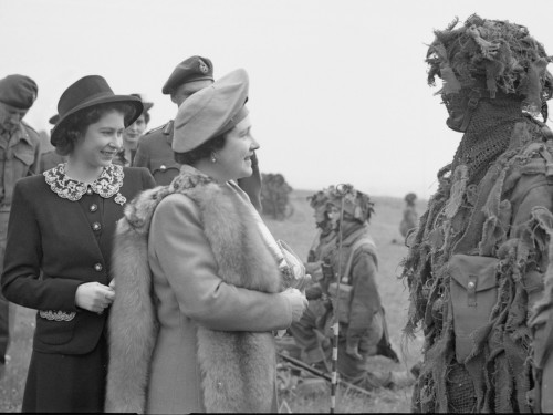 The Queen and Princess Elizabeth talk to a camouflaged sniper during a tour of Airborne forces, UK, 19 May 1944