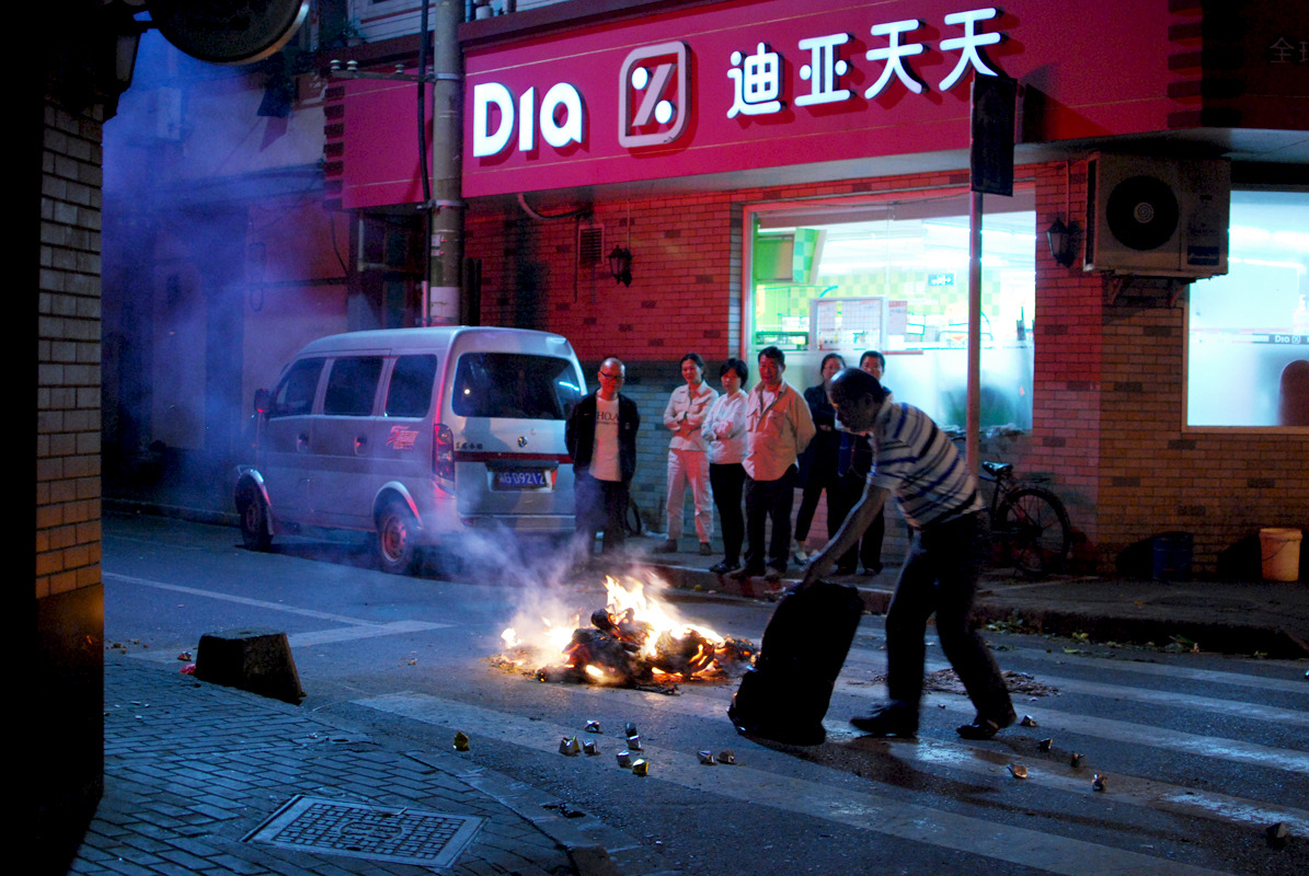 People burning paper money for the dead. Shanghai, China, 2012. Alex Muntean