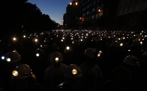 fotojournalismus:  Coal miners demonstrate with their lamps lit through the streets of the city of Leon, northern Spain, on June 12, 2012. Spanish coal miners are staging a nationwide strike action organized by unions opposed to subsidy reductions from 300 million euros to 110 million euros, Agence France Presse reports. [Credit : Cesar Manso / AFP / Getty Images]