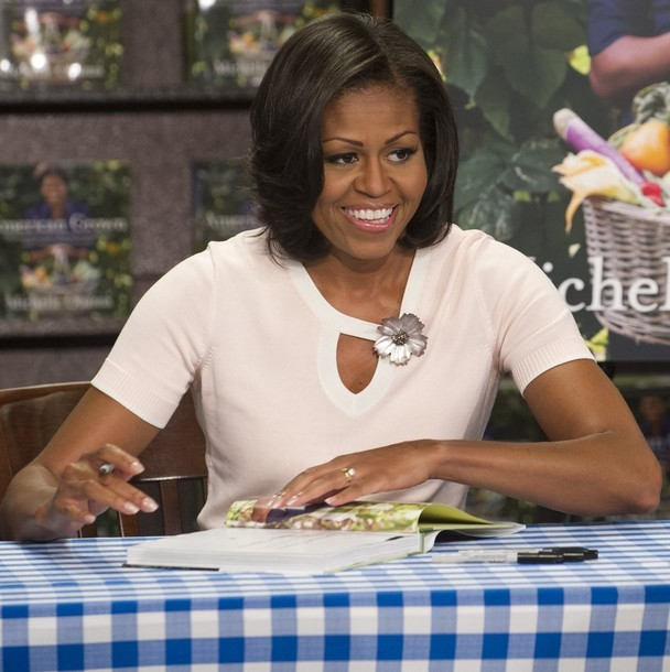 US First Lady Michelle Obama signs her book, 'American Grown: The Story of the White House Kitchen Garden and Gardens Across America' at a Barnes & Noble bookstore in Washington on June 12, 2012. The book's proceeds will go to the National Park Foundation. (via Photo from Getty Images)