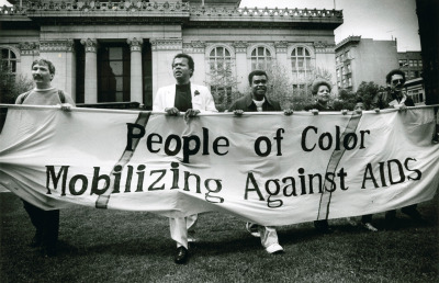 A group of AIDS activists march in front of Oakland City Hall. April 1, 1989. Michael Macor, photographer. Gelatin silver print. Collection of Oakland Museum of California. The Oakland Tribune Collection. Gift of ANG Newspapers.