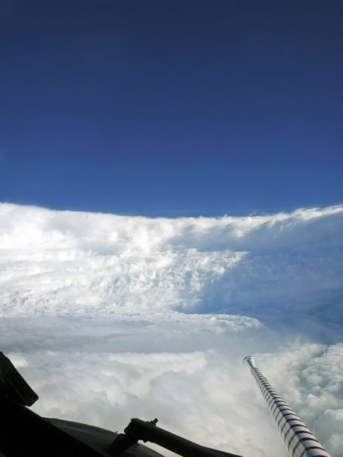"A view from inside the eye of Hurricane Katrina, as Hurricane Hunter instrumentation collects meteorological readings. This eye features a strong ""stadium effect"", with the eyewall resembling bleachers."