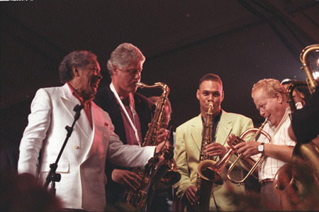 Image description: President Bill Clinton playing the saxophone at the 14th Anniversary of the Newport Jazz Festival in June, 1993. Photo from the National Archives.