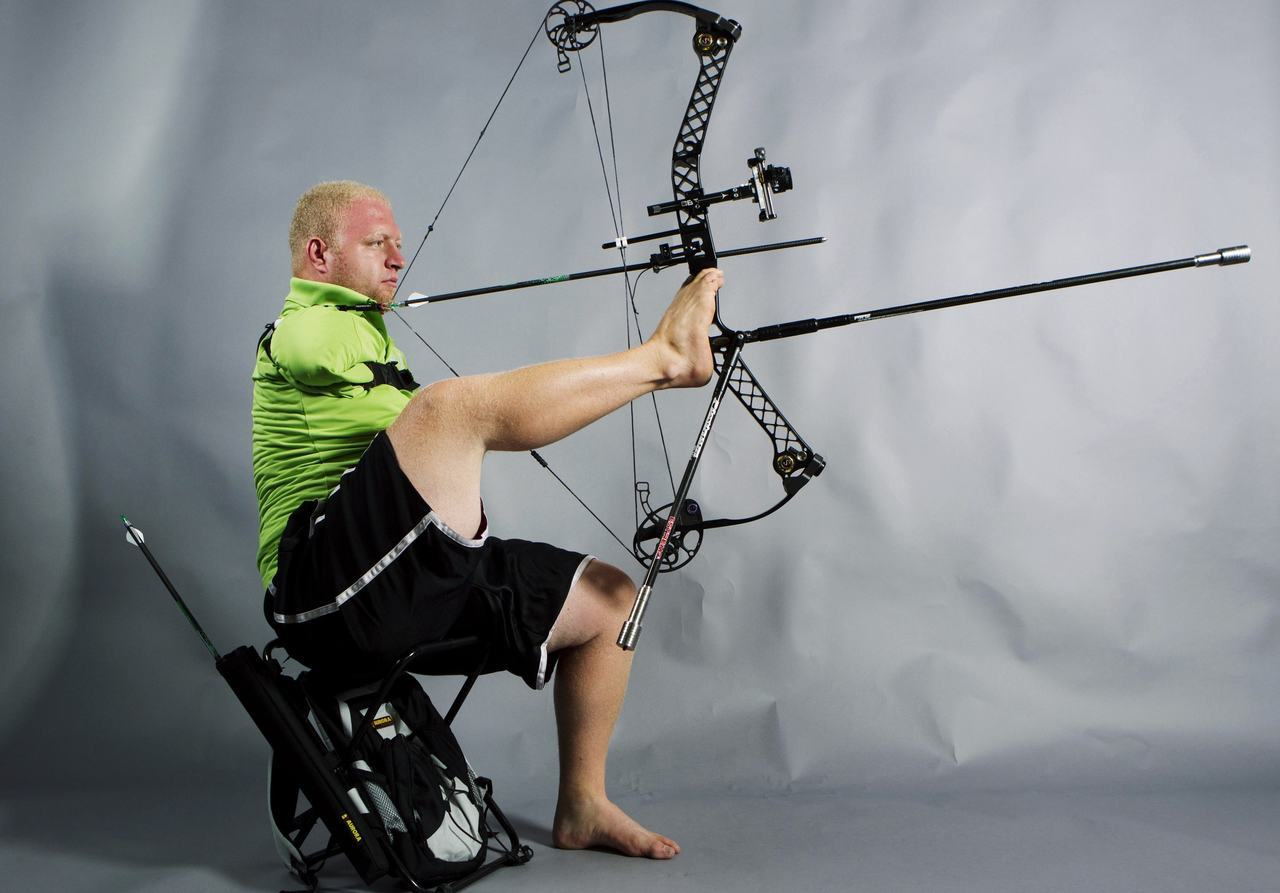 nationalpostsports:  Paralympic archer Matt Stutzman uses his feet to hold and aim his bow while demonstrating his archery technique in New York. Stutzman, who was born without arms, will be representing the U.S. in the upcoming 2012 Paralympic Games in London. REUTERS/Lucas Jackson  That is one serious compound, counter-balanced bow. Impressive! Considering the leg muscles are significantly stronger than arm muscles, I would even surmise that he could put a hefty loft on some arrows.