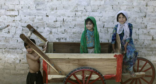 delucazade:  Afghan refugee girls, Nasreen Gul, 5, right, and Yasmine Sadiq, 2, play on a wooden cart left outside a mosque near a slum area on the outskirts of Islamabad, Pakistan, Tuesday, May 29, 2012. AP / Muhammed Muheisen