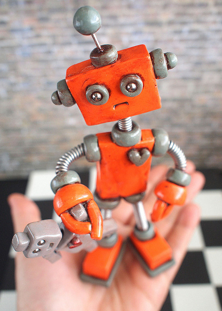 "Robot Sculpture Orange Olie Rustic Bot with Robot Doll - Clay, Wire, Paint on Flickr.Adopt this rustic robot Do not take Olie's much loved dollie, who's name might be Molly. His love of this robot is no hobby. He loves this doll so much, he even got into a scuffle with a bobby. Olie is orange and gray, with a rustic finish, holding a gray robot doll. He stands at 6.5"" inches tall by 3"" inches wide. MY 3 ROBOT LAWS: 1.0: Each Robot is, Unique, one of a kind. 2.0: NOT intended for children, NOT Bendable, it is an art sculpture. 3.0: Not intended for those that do not think robots are awesome. HOW THEY ARE MADE: Each robot is handmade by me. Polymer clay is shaped into robotic goodness, reclaimed bearing balls added for eyes and wire woven into springs that make the neck, arms & legs (coiling gizmo rocks). After baking, multiple coats of varnish are brushed on for protection and shiny delight.twitter.com/robotsawesomefb.com/robotsareawesometheawesomerobots.com"