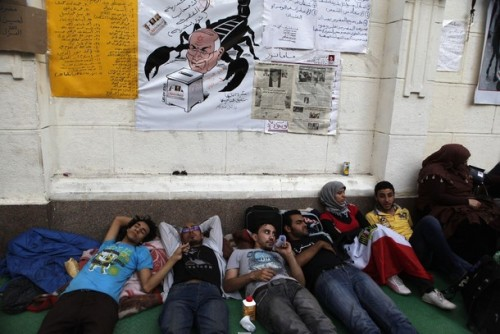 (Reuters) Protesters lie down during a hunger strike in front of Egypt's cabinet office in Cairo June 11, 2012. Around 60 activists are on the sixth day of a hunger strike demanding that former military man Ahmed Shafik is banned from running for president, and for the release of thousands of prisoners held by the military. The protesters say they will continue the hunger strike until June 14, when a court will rule on the validity of a law passed by parliament but not implemented that Mubarak-era officials be banned from participating in politics.