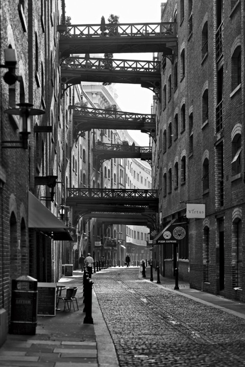 enochliew:  Shad Thames photographed by Rob Telford Wrought-iron bridges that once helped transport goods between inner-ring and dockside factories along the lane are now terraces for families and businesses.