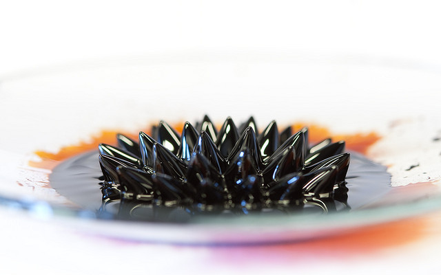 This image shows a ferrofluid - a liquid that is magnetic. It consists of nanometer-sized maghemite particles dispersed in a liquid. Maghemite is γ-Fe2O3, a kind of rust. The maghemite is put on a watch glass, with a magnet placed under it. The so-called spikes point in the direction of the magnetic field of the magnet.