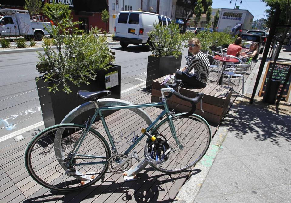 "Boston looks to transform parking spots into small parks  The program turns spaces into ""parklets"" - petite, three-season patios, with benches and planters atop platforms built flush with the sidewalk. (ERIC RISBERG/ASSOCIATED PRESS)"