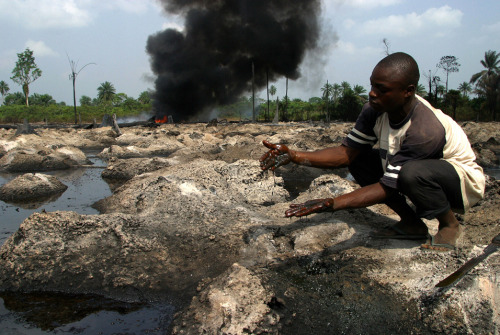 George Osodi, Land Pollution, 2004  A local Nigerian youth scoops crude oil from the ground as he assesses the damage done to farmland by the oil spill in Rukpokwu, near the oil-rich city of Port Harcourt . The ruptured oil pipeline, belonging to Shell Petroleum Development Company exploded, damaging about 300 hectares of community farmlands.