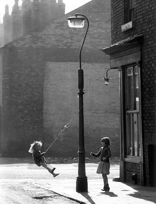 crashinglybeautiful:  Shirley Baker, Girls swinging on a lamppost, Manchester, 1965. Thank you, luzfosca.