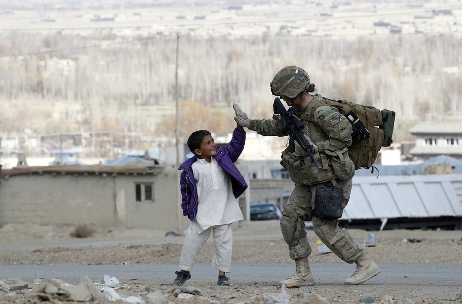 A U.S. Army soldier takes five with an Afghan boy during a patrol in Pul-e Alam, a town in Logar province, eastern Afghanistan.