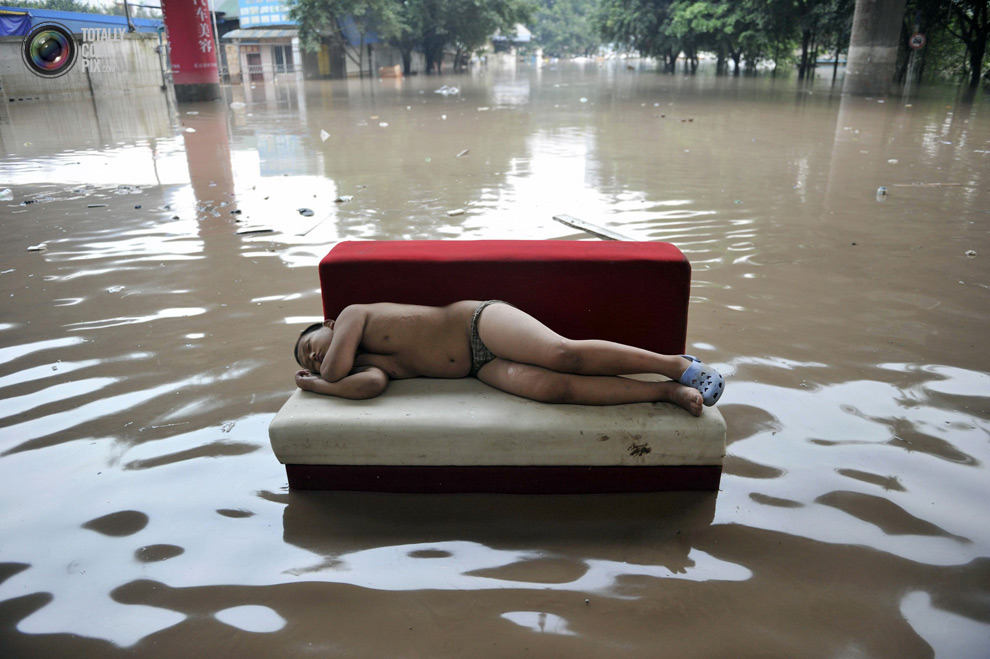 A child sleeps on a couch on a flooded street in Chongqing municipality. Stringer Shanghai / Reuters