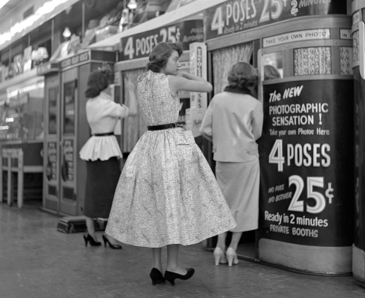 Ladies prepare to have their pictures taken in Manhattan photo booths, 1954. By Frank Oscar Larson