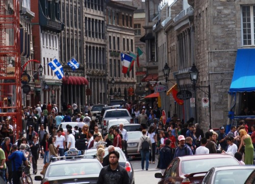 A crowded rue St Paul Est in Vieux Montreal Hey, I can't afford lunch so give me a bite of that donut.