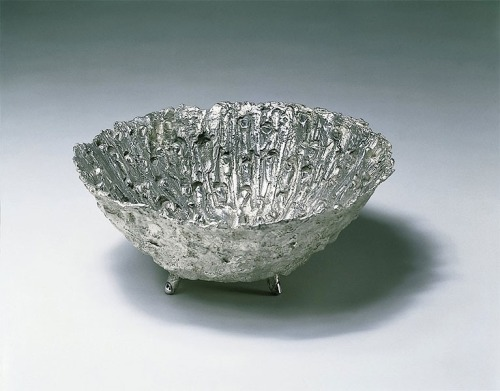 Fingerbowl by Kiki Smith 6¾ x 15 x 15 in. (17.2 x 38.1 x 38.1 cm.) Executed in 1995. Kiki Smith's solid silver Finger Bowl continues the artists concern with the human body. The bowl, supported by a tripod of fingers, is lined on the interior with fingers coming through the form creating a touchingly powerful work. The form originates as a convex dome of clay, the surface of which is gouged and scratched by fingers. The clay is then covered with wax and the inside of the resulting concave wax form has fingers protruding up from the surface. This wax bowl is then cast in fine silver (purer than sterling) by Dominick Ranieri Sculpture Casting in New York. This piece was first conceived by the artist in 1986. At that time she could only make a wax mold of the work but has always been anxious to see it completed in silver. This is the first opportunity for her to see this, her vision, realized. The edition is limited to 25 and is signed and numbered on the bottom. Every wax mold is hand chased by the artist making each piece unique.