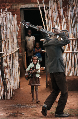 afro-art-chick:  Father and Daughter Playing Guitars A worker on the farm of Afrikaner Johan Richter plays the guitar with his daughter on a Sunday morning before he goes to work as a field hand. The father works 60 hours a week for a salary of $30 a month. © David Turnley/CORBIS