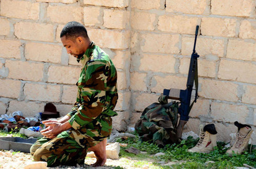 A Libyan soldier praying in Brega, Libya